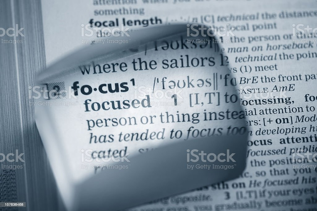 Dictionary word focus in a magnifying glass stock photo