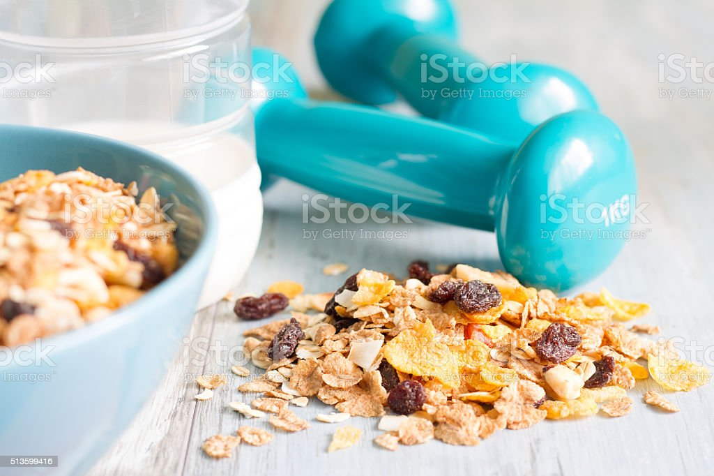 Diet and fitness concept with dumbbells and muesli stock photo