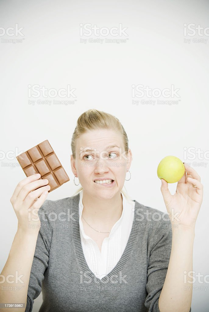 Diet Choice with Woman holding Chocolate and Apple royalty-free stock photo