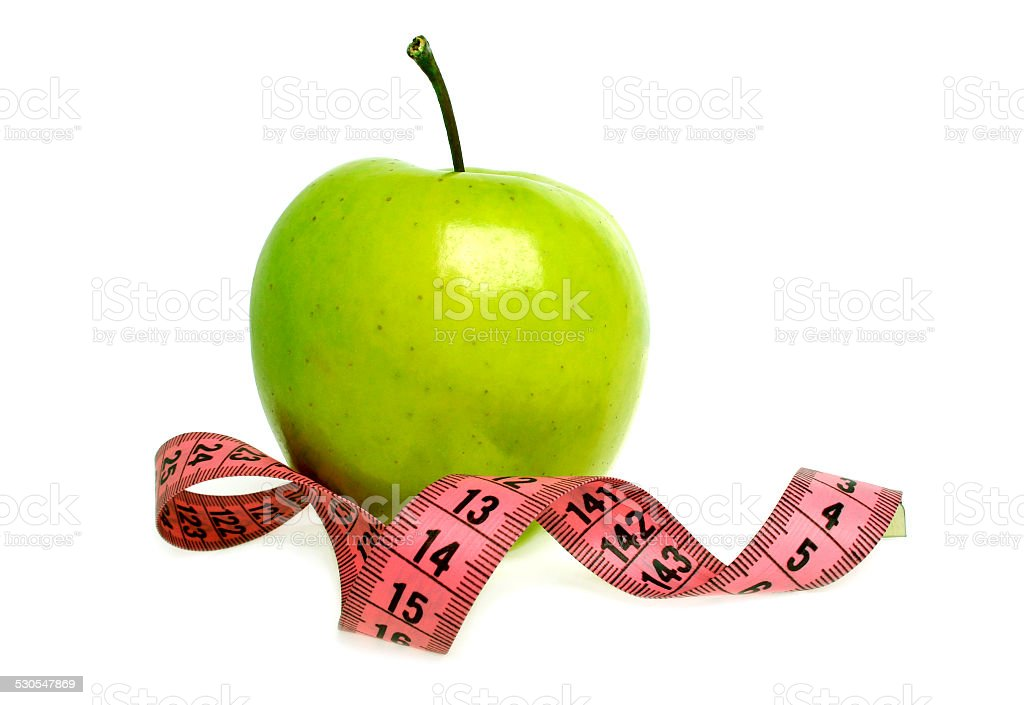 Diet concept - green apple and measuring tape stock photo