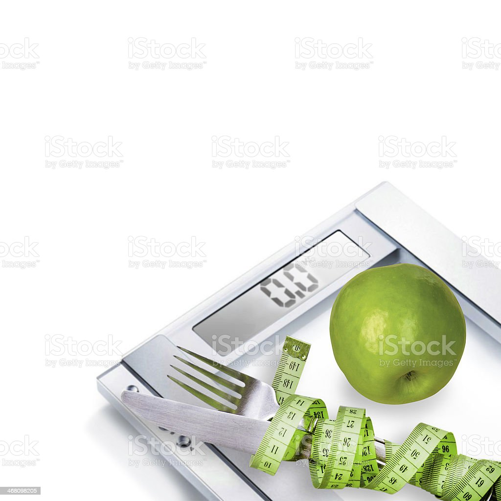 Diet concept. Scales, cutlery and green apple. royalty-free stock photo