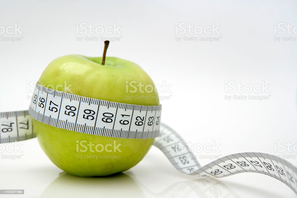 Diet concept with green apple and a tape measure royalty-free stock photo