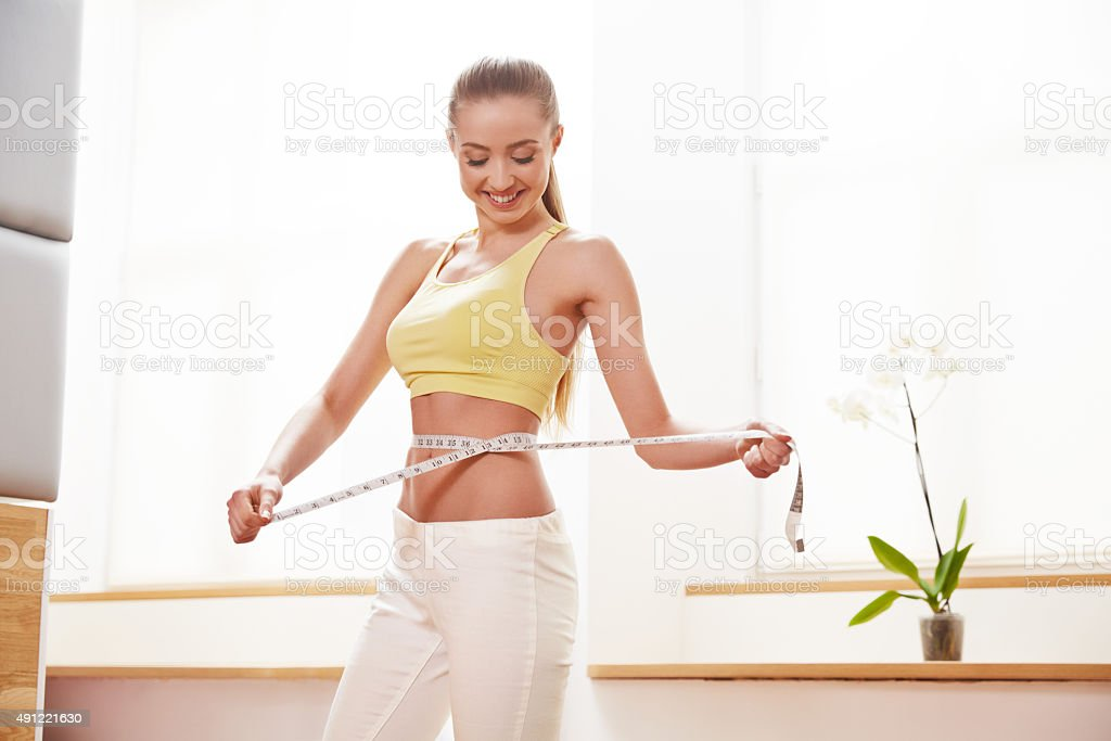 Diet. Dieting concept. Woman in Sportswear Measuring Her Waist stock photo