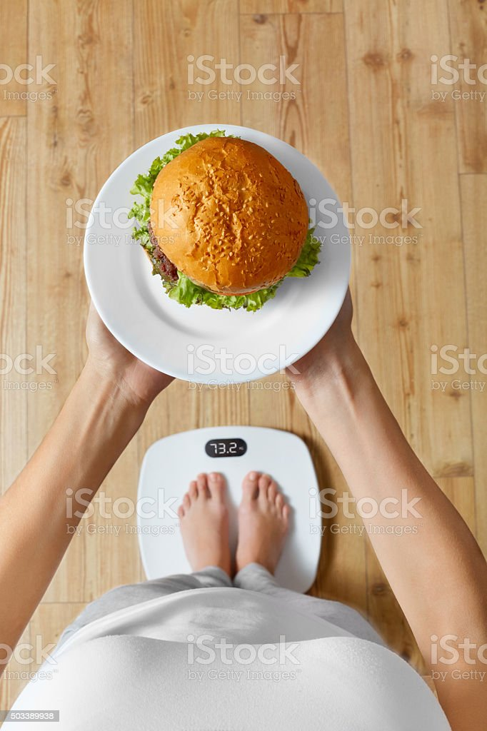 Diet, Fast Food. Overweight Woman On Scale, Hamburger. Junk Food stock photo