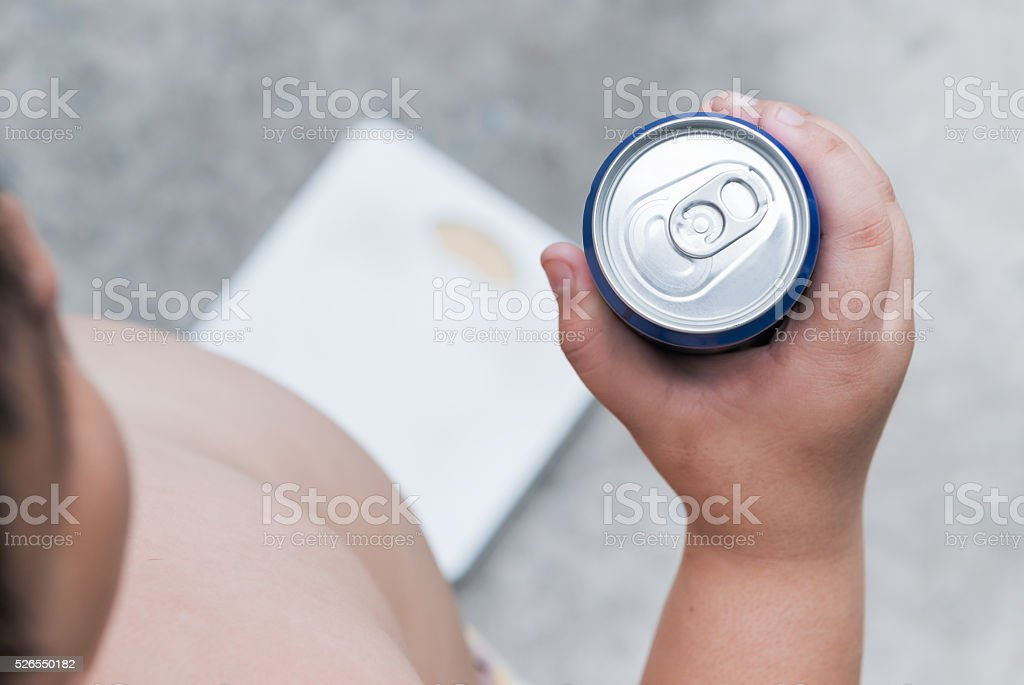 Diet. fat boy holding soft drink can. stock photo