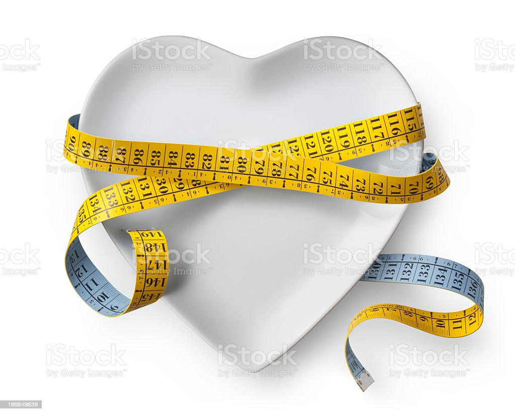 Diet. Heart shaped dish with measuring tape. royalty-free stock photo