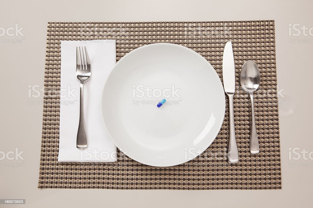 Diet pill alone on a plate. stock photo