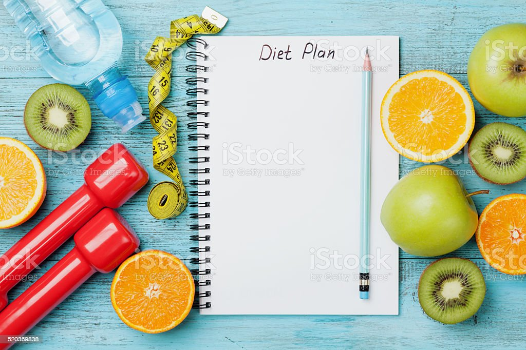 Diet plan, tape measure, water, dumbbells and fruits, detox concept stock photo