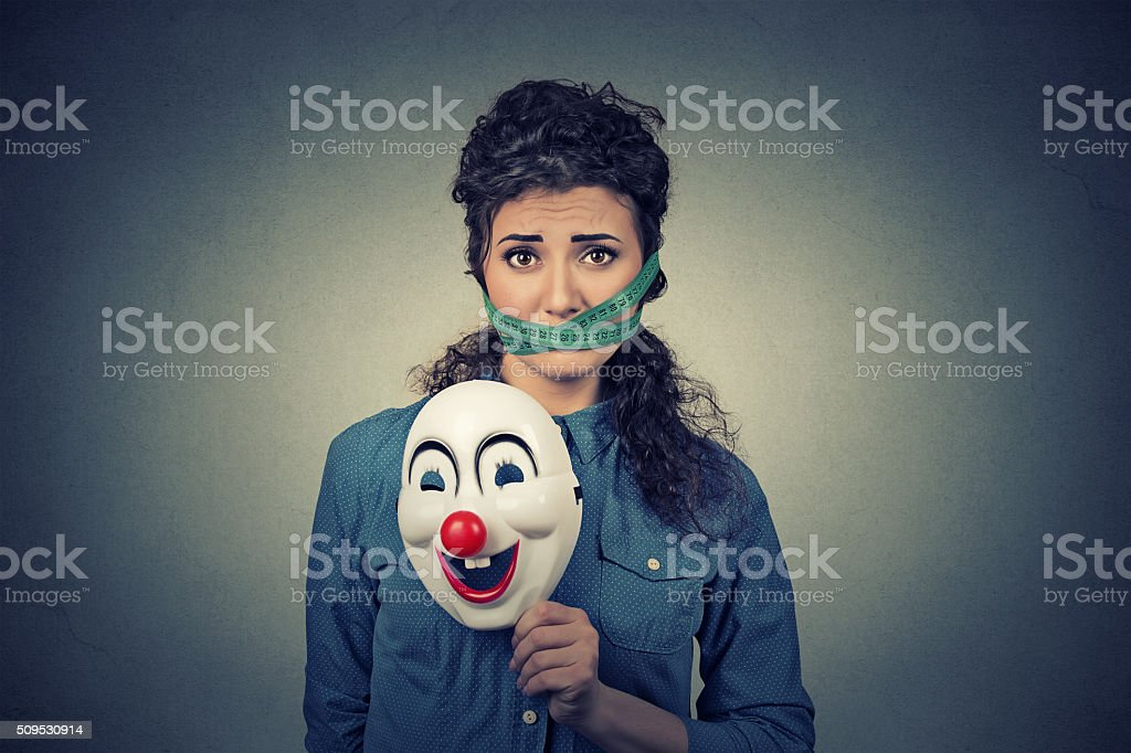 Diet stress. Woman with clown mask measuring tape around mouth stock photo