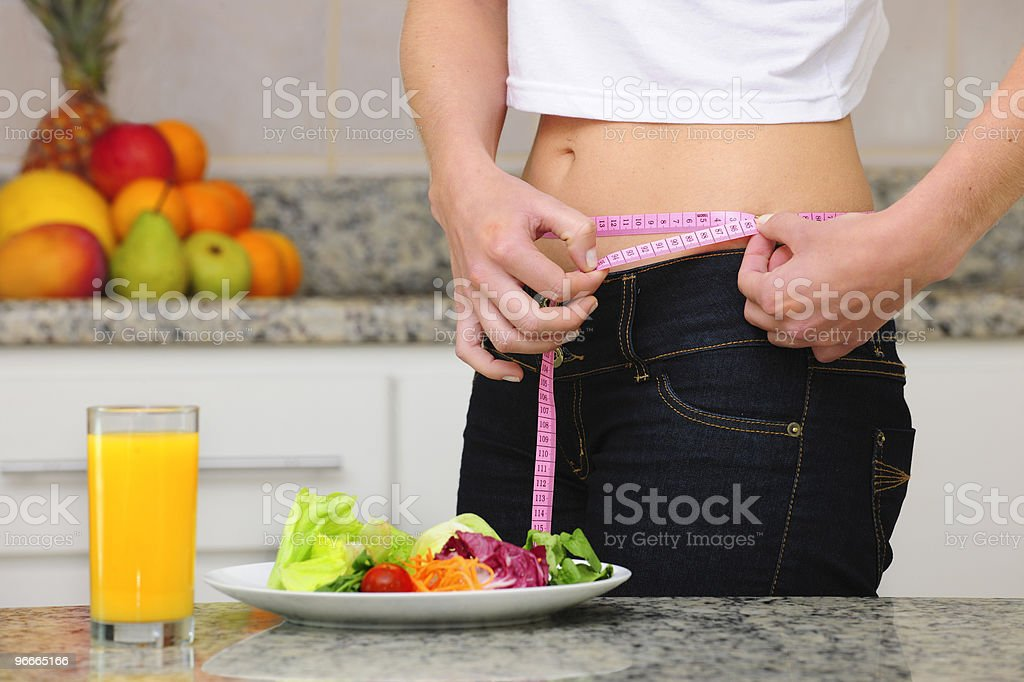 diet: woman with salad and measuring tape stock photo