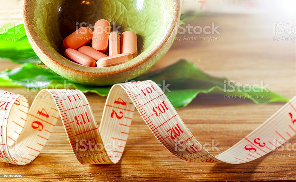 Dietary pills vie centimeter. The concept of diet, health stock photo