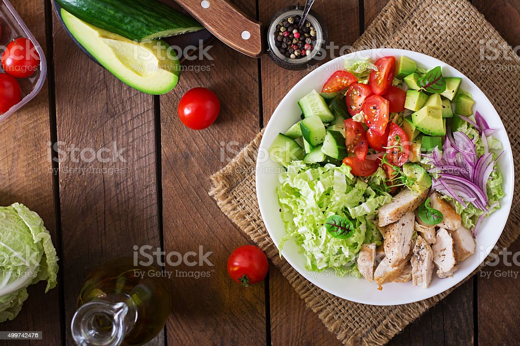 Dietary salad with chicken, avocado, cucumber and tomatoes stock photo