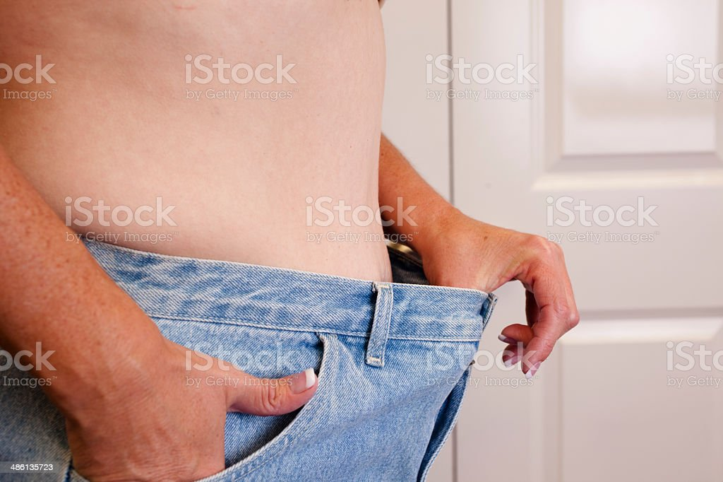 Dieting woman shows off her smaller waist size. royalty-free stock photo