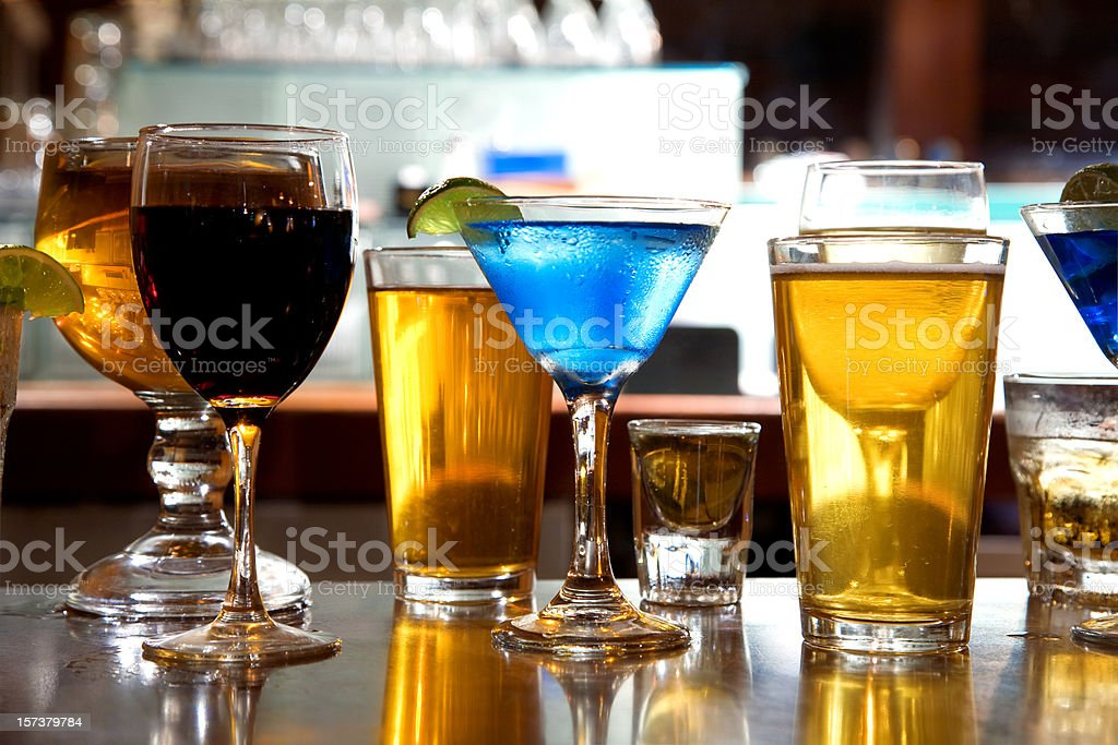 Different alcohol drinks sitting on a bar stock photo