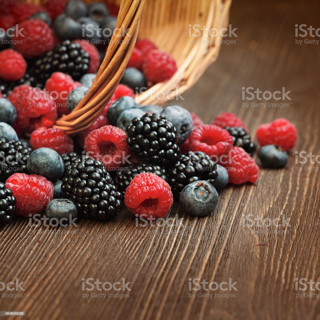 different berries  in a basket on a wooden table stock photo