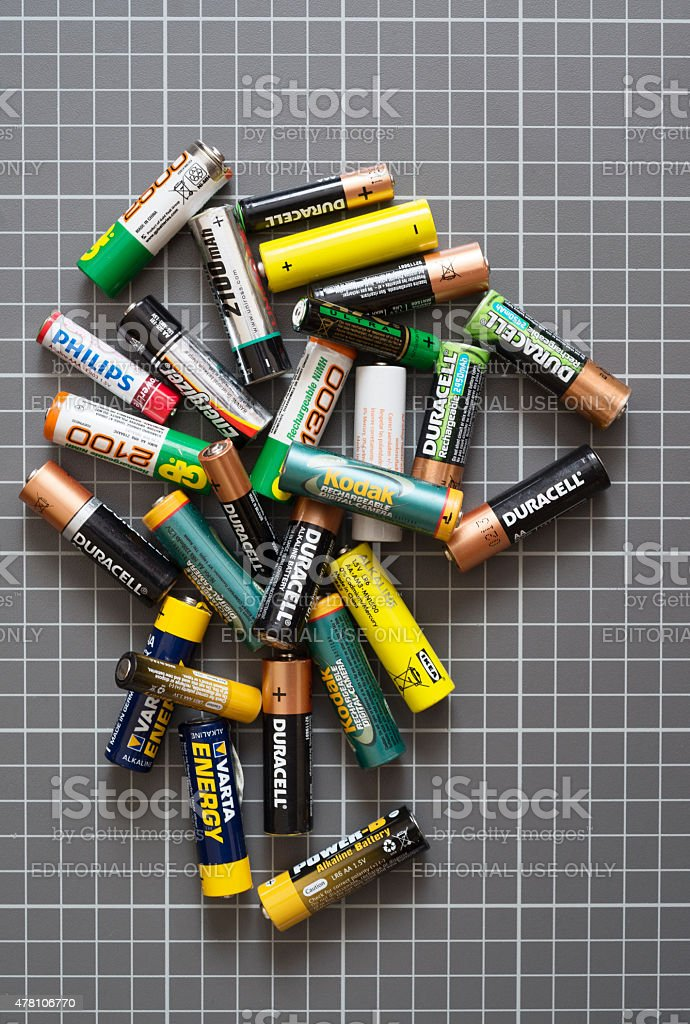 Different brand batteries on the grey plate stock photo