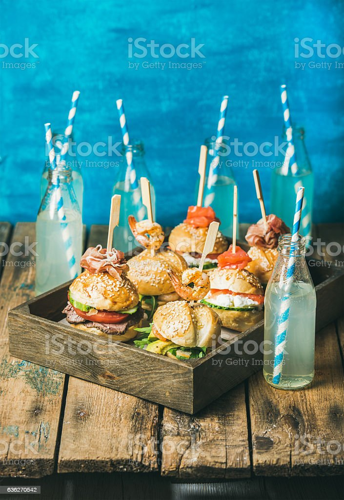 Different burgers with sticks in wooden tray and fresh lemonade stock photo