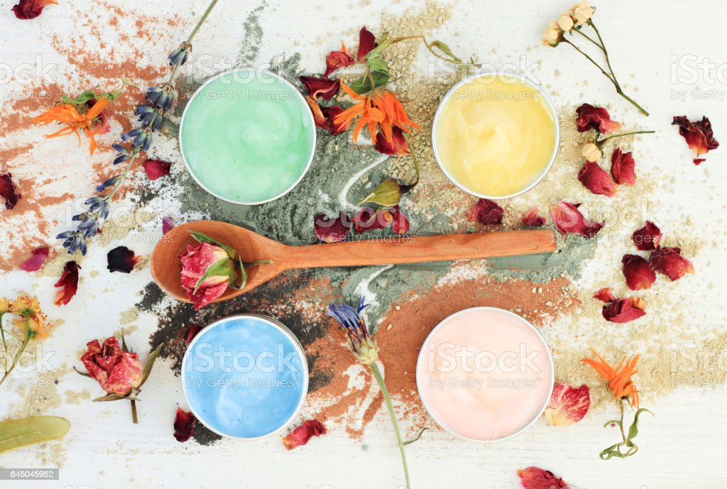 different clay facial masks in jars, powder and dried herbs stock photo