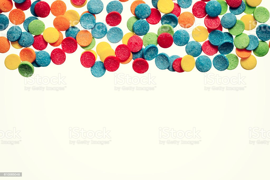 Different color confetti placed on white background. stock photo