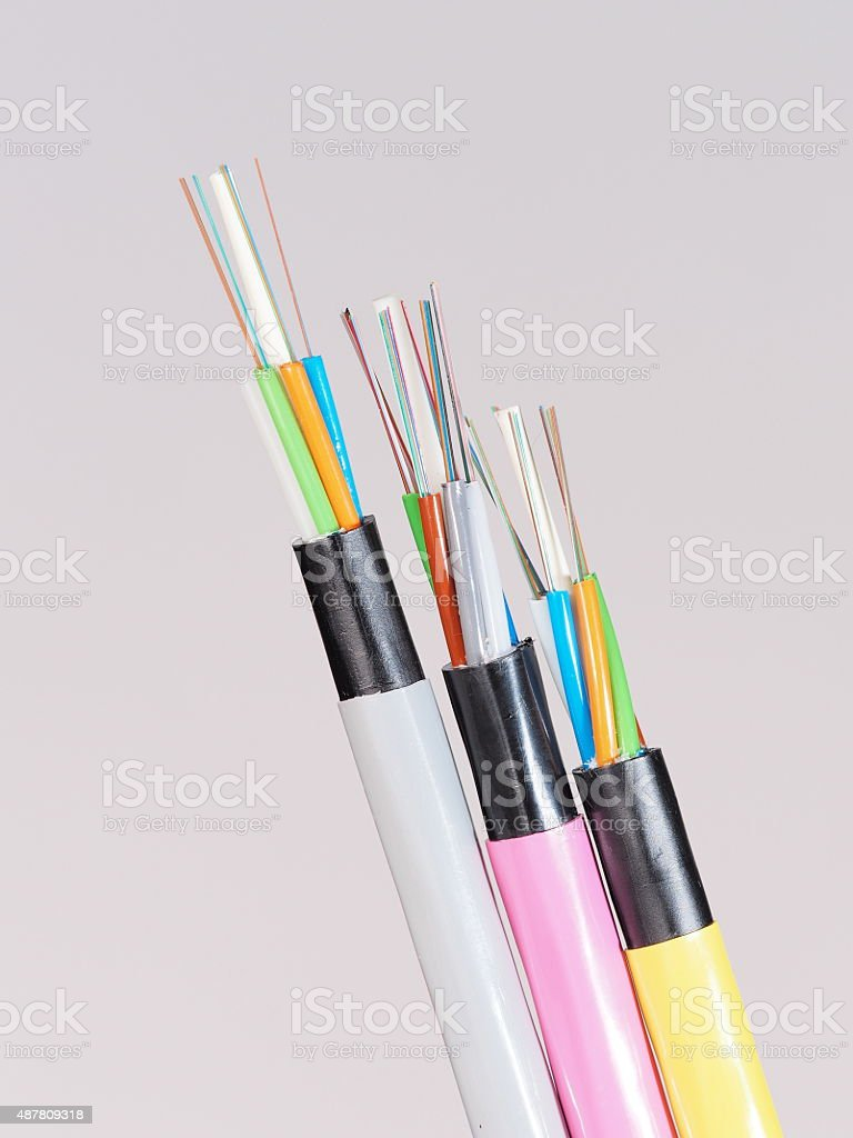 Different colored fiber optic cable ends with stripped jacket layers stock photo