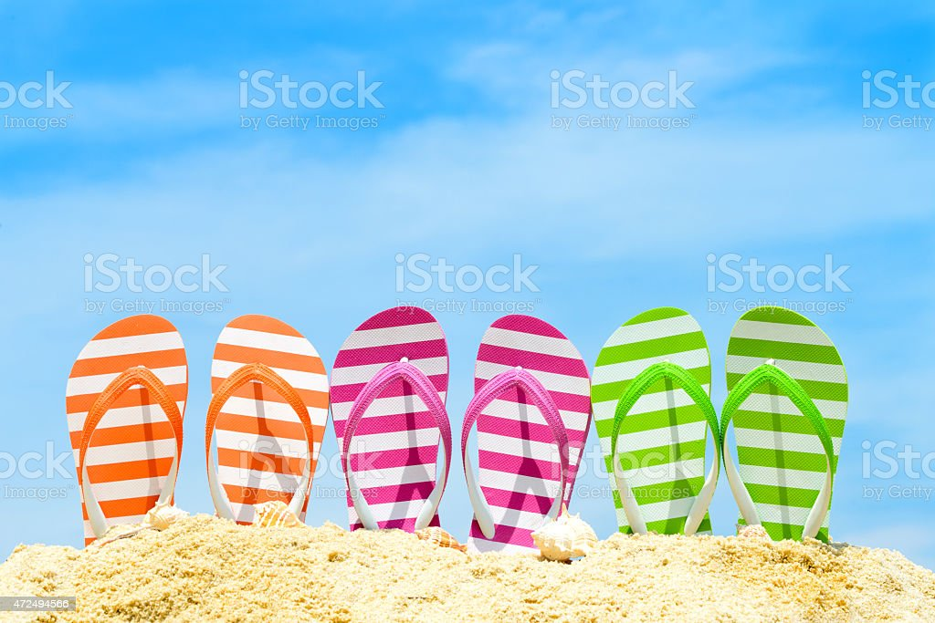 Different colored flip flops in the sand stock photo