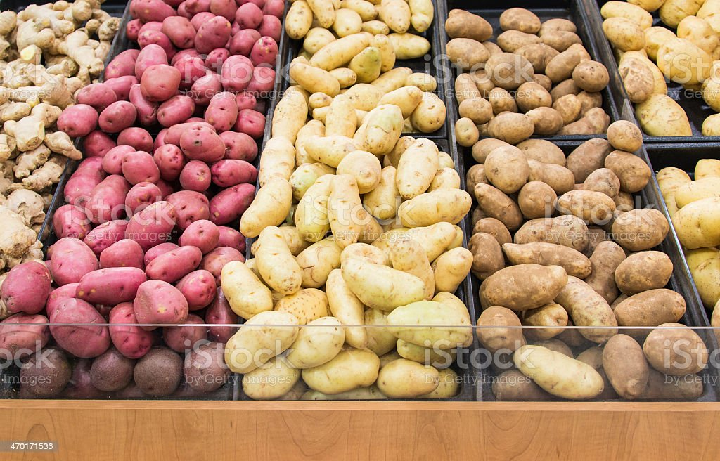 Different colors and varieties of potatoes in a grocery store stock photo