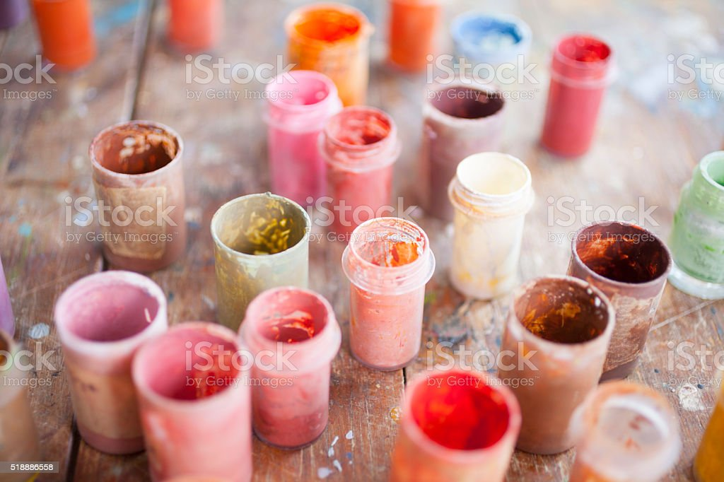 Different colors of oil paints in cans on table stock photo