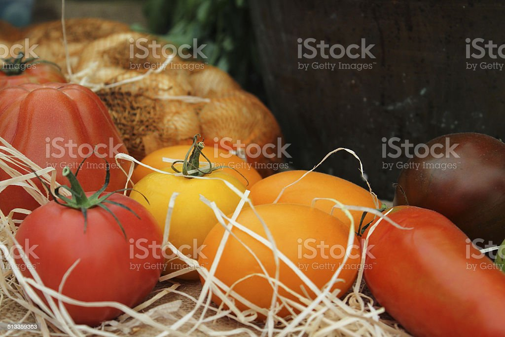 Different colour tomatoes, homegrown, red, yellow, orange, purple, onions stock photo