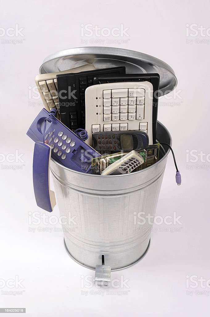 different computer parts and phone in trash can royalty-free stock photo