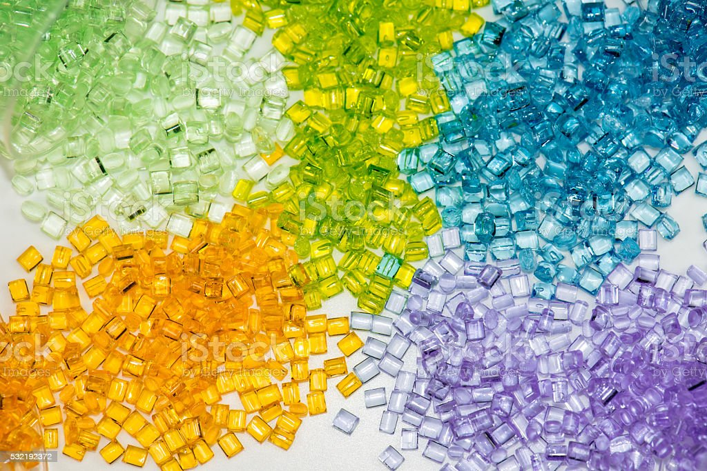 different dyed polymer granulates stock photo
