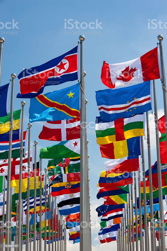 Different flags of various countries flying from a flag pole royalty-free stock photo