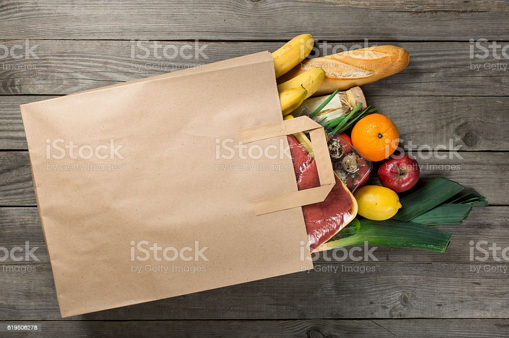 Different food in paper bag on wooden background, close up stock photo