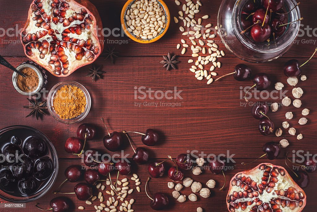 Different fruit and spices on red wooden table top view stock photo