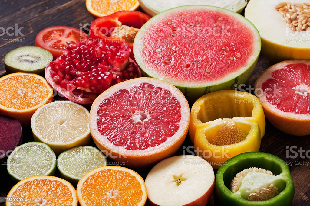 Different furits and vegetables, halved, on wood stock photo