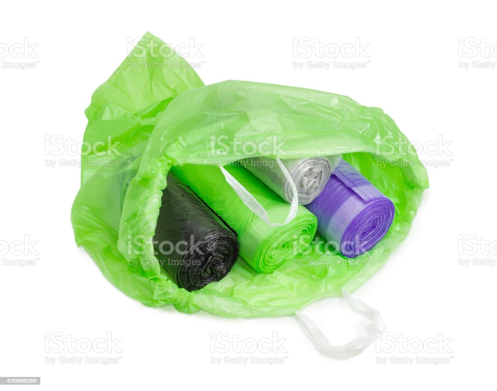 Different garbage bags in rolls in open green garbage bag stock photo