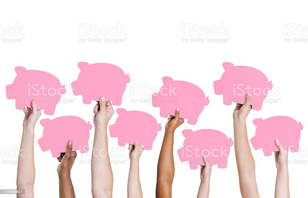 Different hands holding up cutouts shaped like a piggy bank stock photo