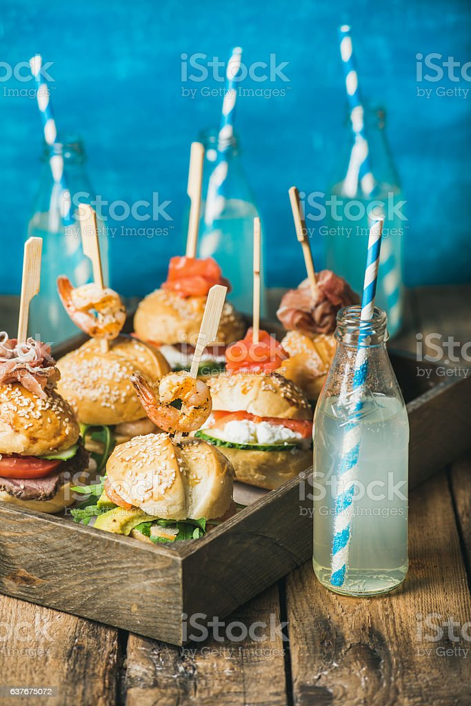 Different homemade burgers with sticks in wooden tray and lemonade stock photo