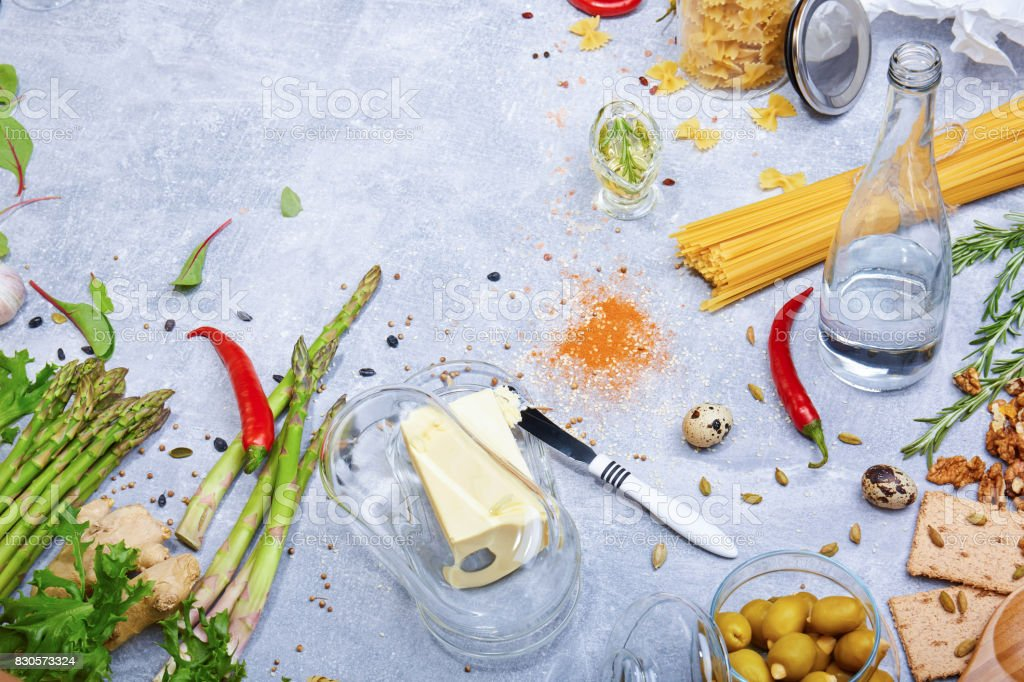 Different ingredients on a table background. Butter with a knife and spices. Fresh greens and pepper. Pasta preparation. stock photo
