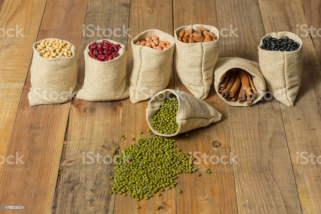 Different kinds of beans and cinnamon in sacks bag royalty-free stock photo