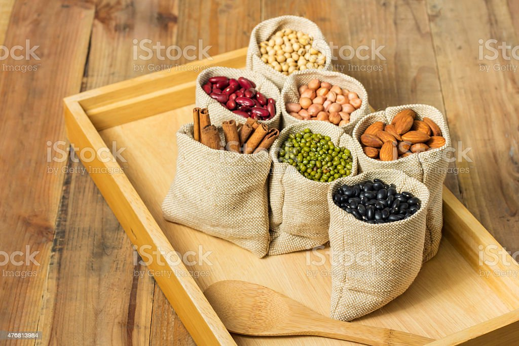 Different kinds of beans in sacks bag on wooden background royalty-free stock photo