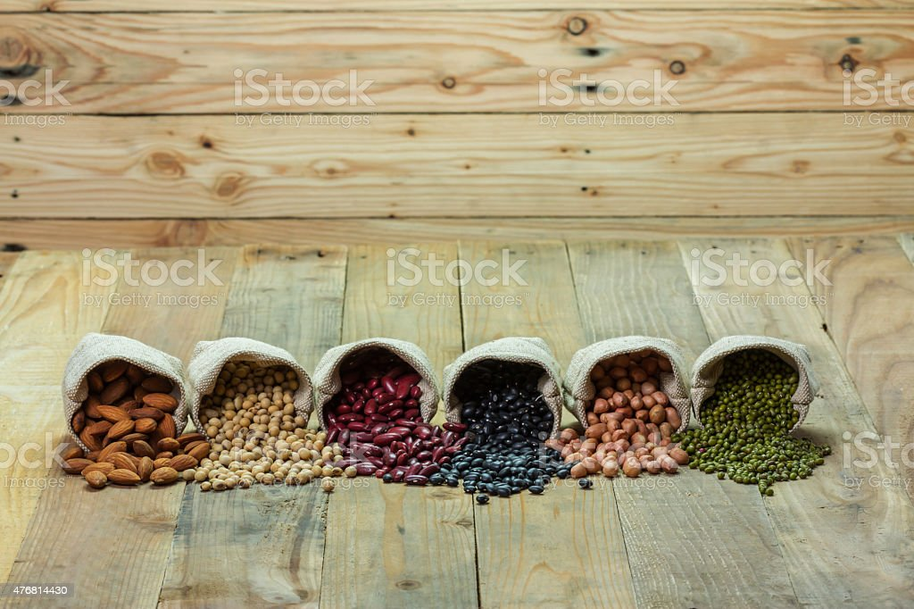 Different kinds of beans scattered on wooden background royalty-free stock photo
