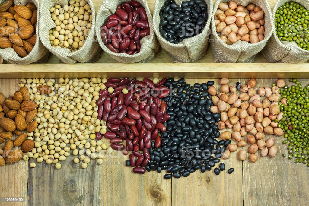 Different kinds of beans scattered on wooden background stock photo