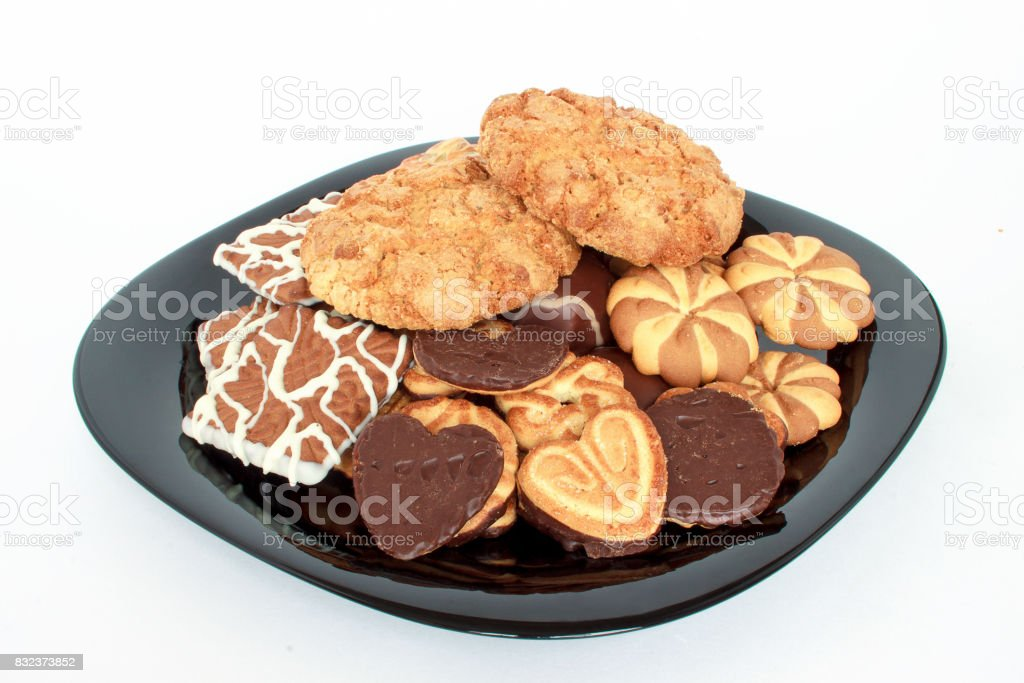 Different kinds of delicious cookies on a big black plate. stock photo