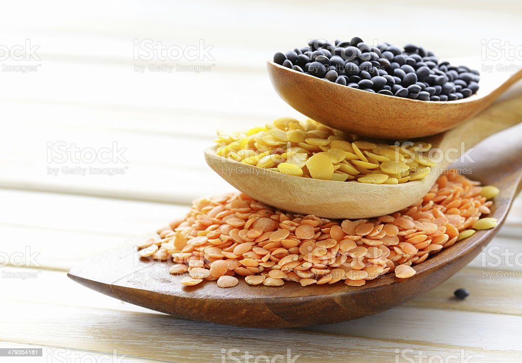 different kinds of lentils in wooden spoons stock photo