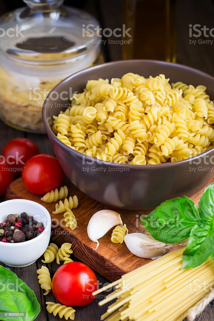 Different kinds of pasta, cherry tomatoes and spices stock photo