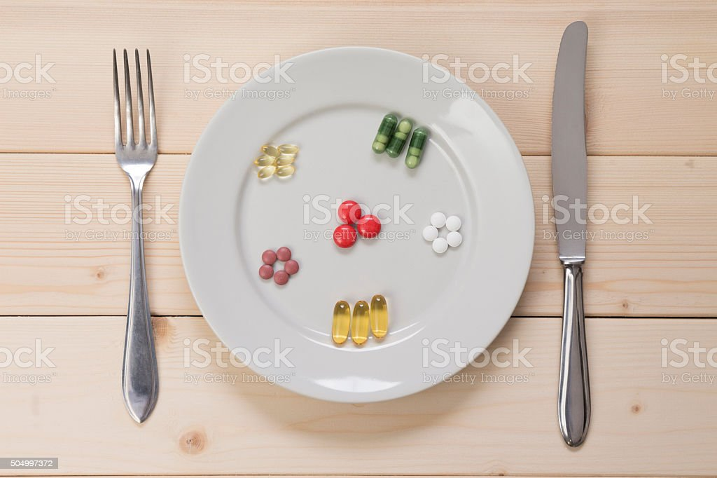 Different kinds of pills on plate and fork with knife. stock photo