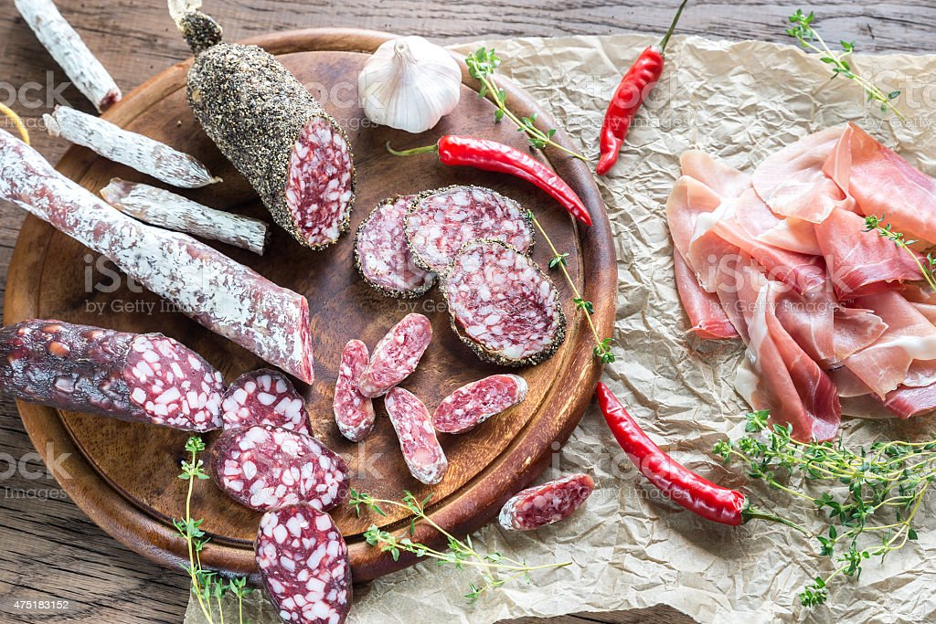 Different kinds of sausage on the wooden background stock photo