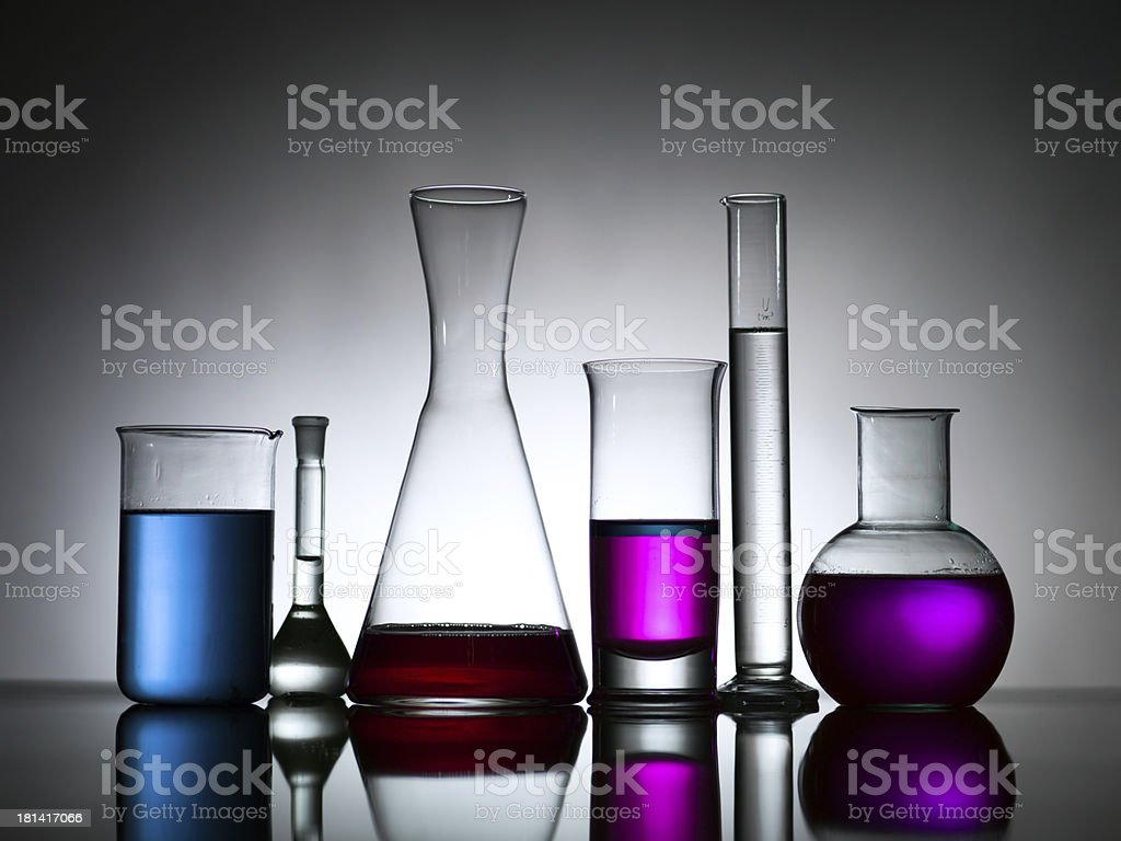 different lab bottles filled with colored substances stock photo