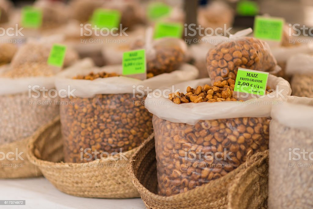 different nuts in bags on a market for selling stock photo