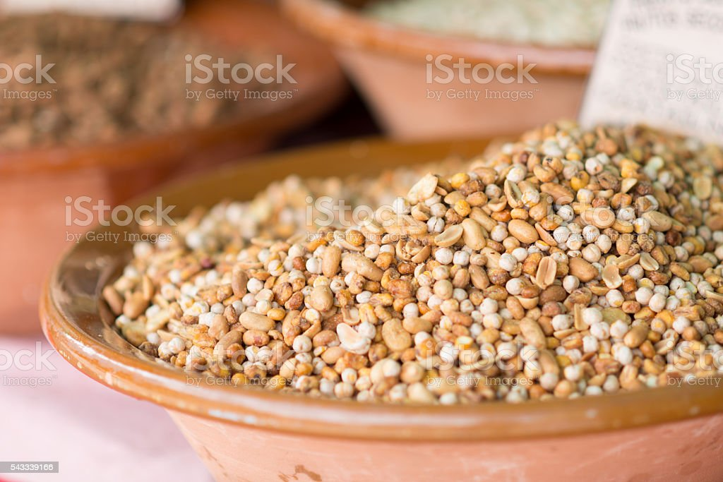 different nuts in bowls on a market for selling stock photo